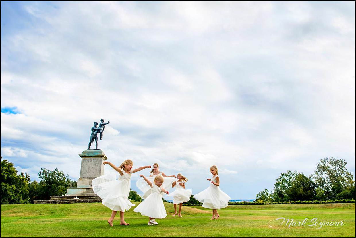 Berkshire Wedding Photographer Mark Seymour captures the young bridesmaids as they dance on the lawn at Cliveden House