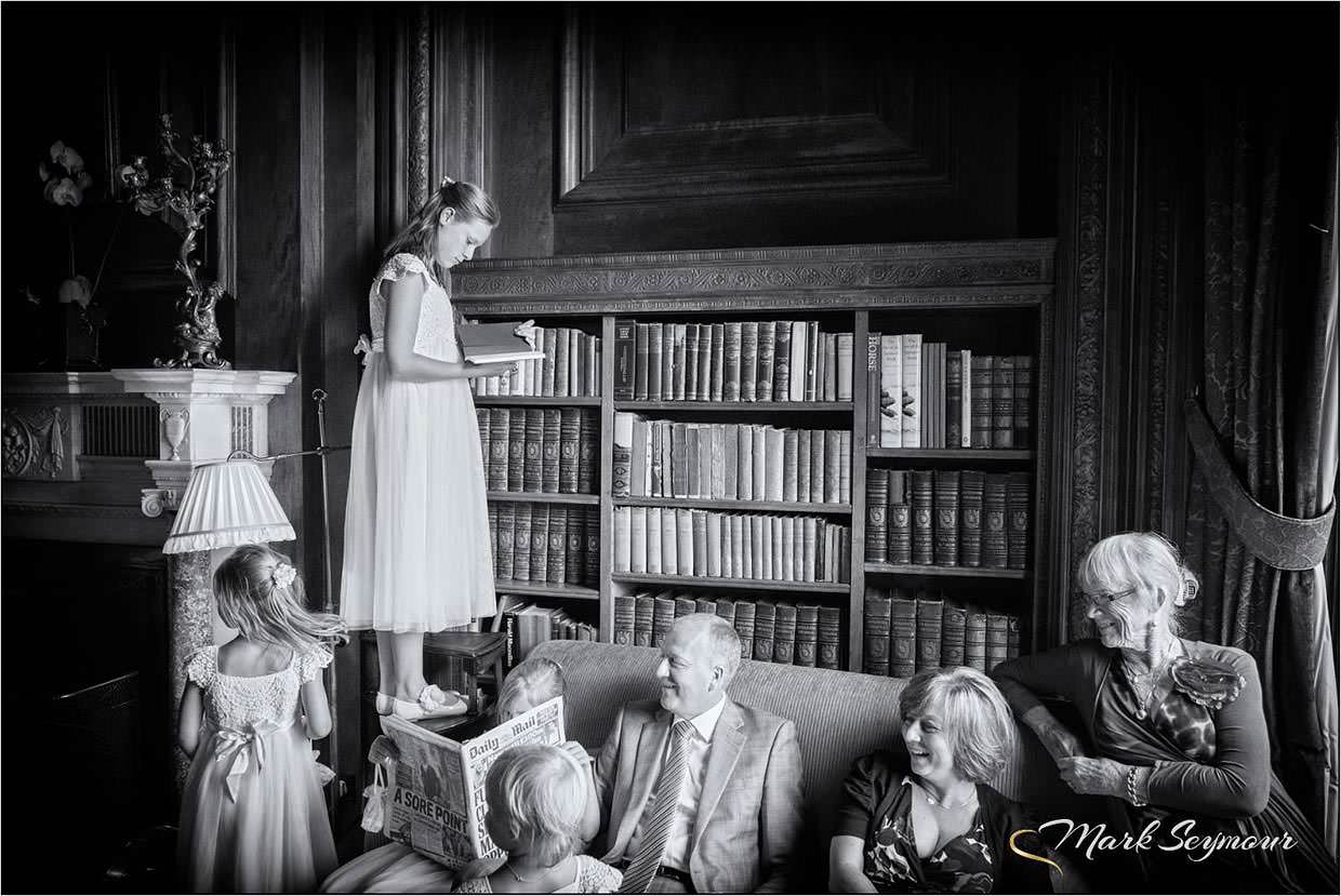 Young bridesmaid in the library at Cliveden House a reportage image by Berkshire Wedding Photographer Mark Seymour