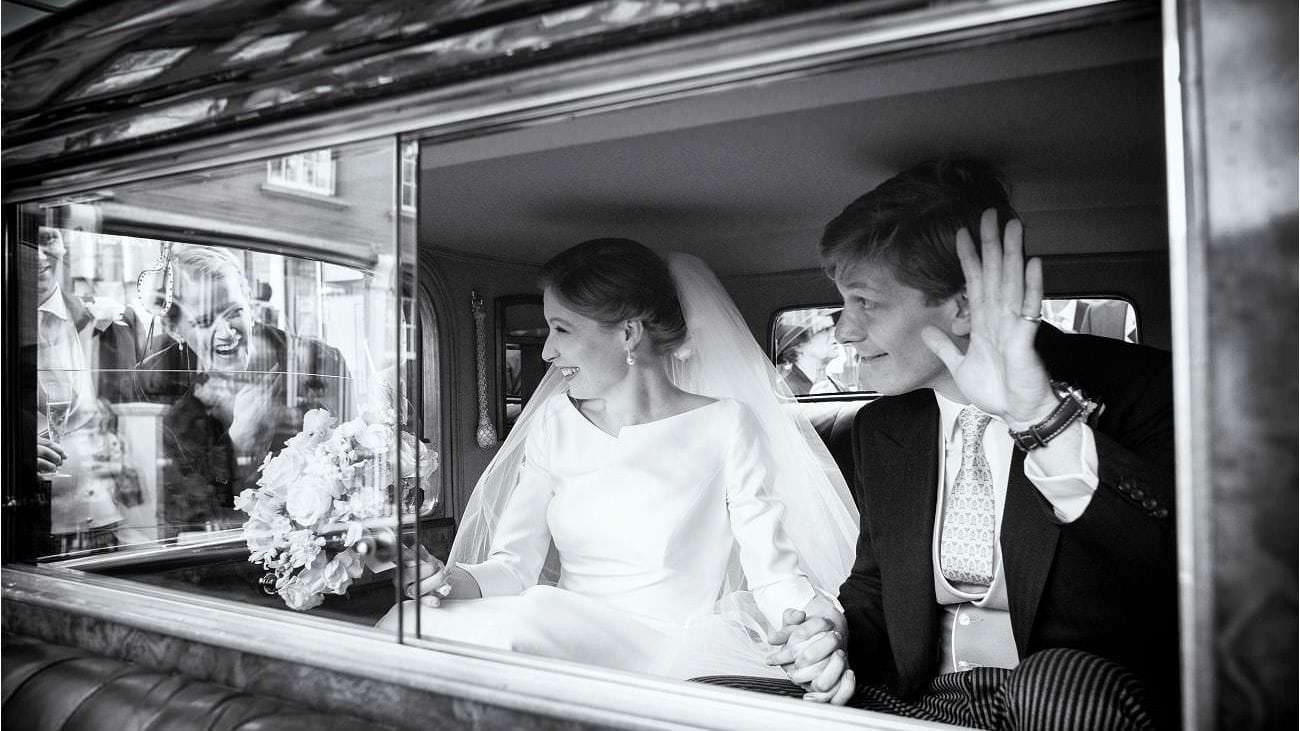Wedding couple wave in their wedding car