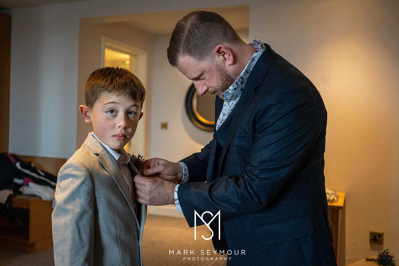 Groom getting son ready at Le Manoir